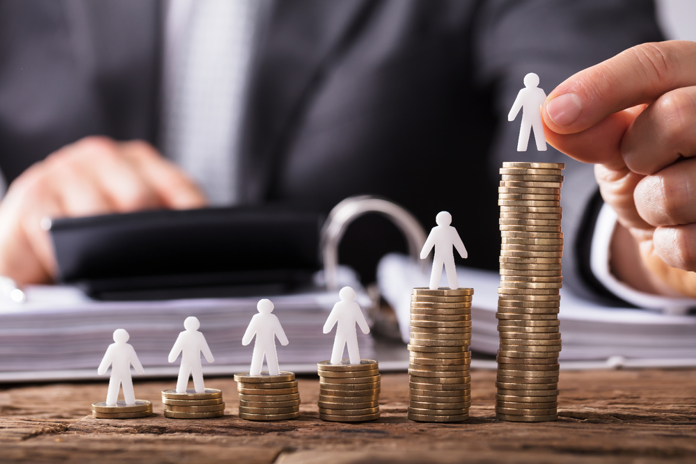 Human Hand Placing Small Human Figure On Increasing Stacked Coins Over Wooden Desk